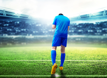 Rear view of asian football player man celebrate his goal standing on football field at stadium Stockfoto