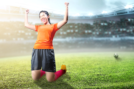 Asian football player woman celebrate her goal with raised arms and kneeling on the football field at stadium Stockfoto