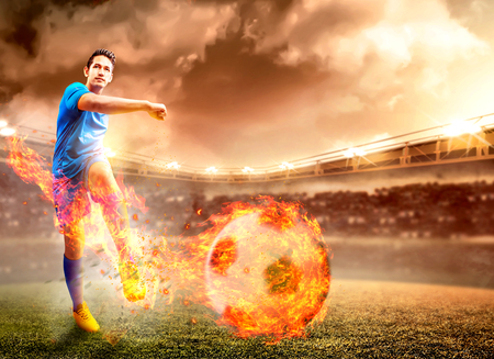 Asian football player man in blue jersey with kicking the ball with fire effect on the football field at stadium Stockfoto