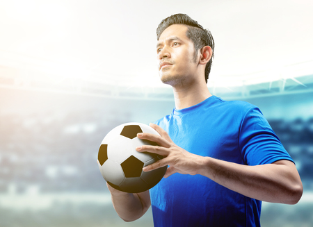 Asian football player man in blue jersey holding the ball on the football field at stadium
