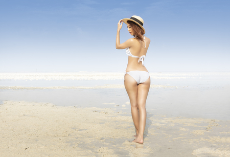 Rear view of asian sexy girl with hat and bikini on the beach. Summer vacation