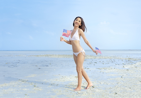 Asian sexy girl in white bikini holding a little american flag on her hands on the beach. 4th of July Independence day concept
