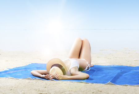 Asian sexy girl in bikini and hat lying on the carpet in beach. Summer vacation
