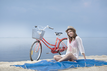 Asian sexy girl with hat sitting on the carpet in beach with bike behind it. Summer vacation