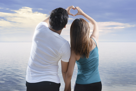 Rear view of asian romantic couple making heart shapes with fingers on the beach. Summer vacation Stockfoto