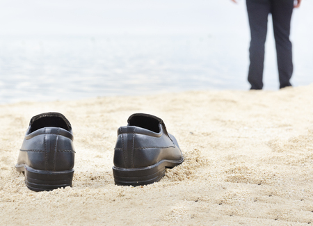 Businessman take off his shoes on the beach. Summer vacation