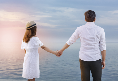 Rear view of asian romantic couple holding hands together on the beach. Summer vacation Stockfoto