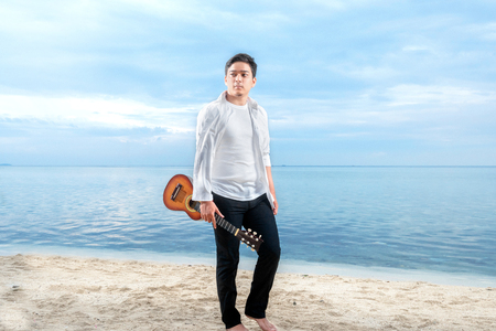 Asian businessman in white clothes holding guitar on the beach. Summer vacation Stockfoto