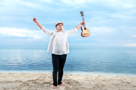 Asian businessman in hat and white clothes raised both hands while holding guitar on the beach. Summer vacation