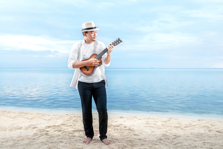 Asian businessman in hat and white clothes playing guitar on the beach. Summer vacation