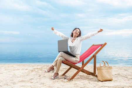 Asian business woman relax when working with laptop sitting in the beach chair on beach. Summer vacation Stockfoto
