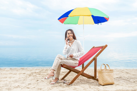 Asian business woman talking on mobile phone while sitting sitting in the beach chair with colorful umbrella on beach. Summer vacation