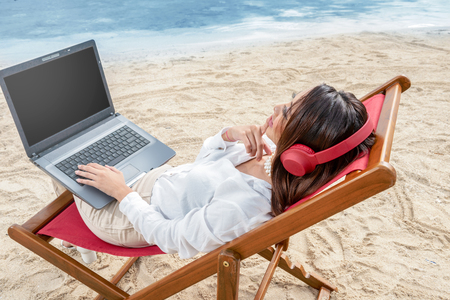 Rear view of asian business woman working with laptop while using headphones sitting in the beach chair and thinking something on beach. Summer vacation Stockfoto