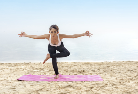 Asian healthy woman practicing yoga on the carpet in beach. Healthy concept Stockfoto