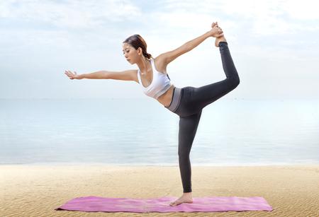 Mujer sana asiática practicando yoga en la alfombra en la playa. Concepto saludable