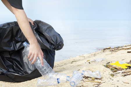 Hand man with garbage bag picking up plastic bottle on the beach. Environmental cleaning concept Stockfoto