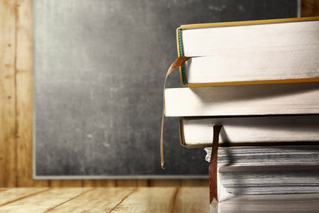 Close up view of pile of books on wooden table with blackboard background. Back to School concept Imagens