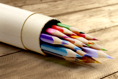 Rolled cardboard with colorful stationery of pencils for drawing on wooden table. Back to School concept Stockfoto