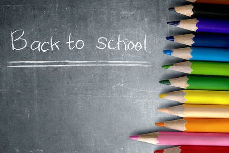 Row of colorful stationery of pencils for drawing on blackboard with Back to School message. Back to School concept