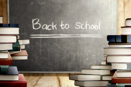Close up view of pile of books on wooden table and blackboard with Back to School message. Back to School concept Stockfoto