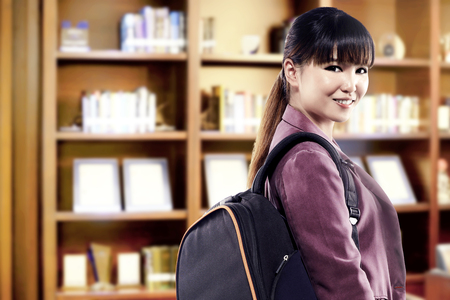 Asian student woman with backpack standing and look back in the university library. Back to School concept Stockfoto