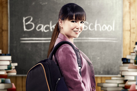 Asian student woman with backpack standing and look back in the classroom with piles of books and blackboard background. Back to School concept