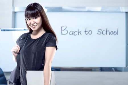 Asian student woman with backpack carrying book in the classroom with message of Back to School on the whiteboard. Back to School concept Stockfoto
