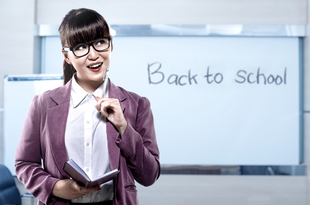Asian student woman with notebook and pen thinking something in the classroom with message of Back to School on the whiteboard. Back to School concept