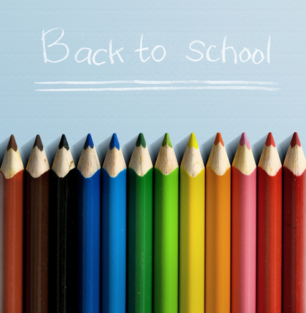 Row of colorful stationery of pencils for drawing on blue table with Back to School message. Back to School concept Stockfoto