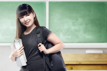 Asian student woman with backpack carrying book in the classroom with chalkboard background. Back to School concept