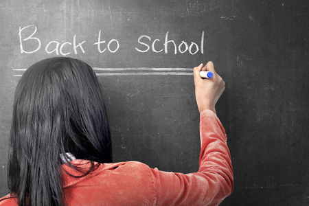 Rear view of asian student woman writing Back to School on the blackboard. Back to School concept