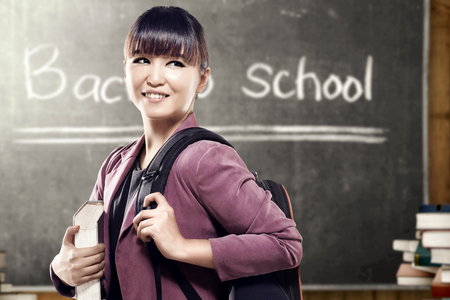 Asian student woman with backpack carrying book standing and look back in the classroom with piles of books and blackboard background. Back to School concept