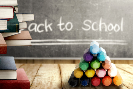 Close up view of pile of books and colorful crayons on wooden table and blackboard with Back to School message. Back to School concept Stockfoto