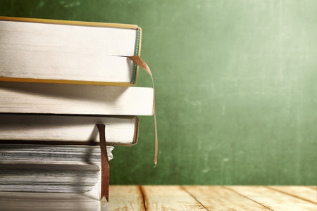 Close up view of pile of books on wooden table with chalkboard background. Back to School concept Zdjęcie Seryjne - 122472056