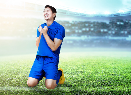 Asian football player man celebrate the goal with holding his jersey and kneeling on the football field at stadium Stok Fotoğraf