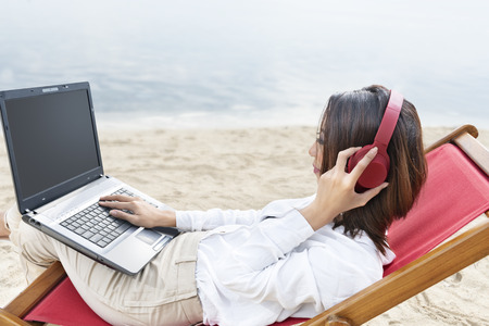Asian business woman working with laptop while using headphones sitting in the beach chair on beach. Summer vacation