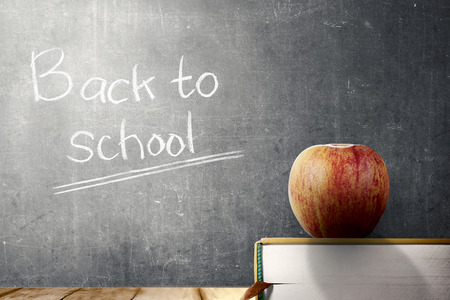 Close up view of book with apple on wooden table and blackboard with Back to School message. Back to School concept