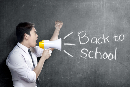 Asian teacher man using megaphone to notify for go back to school with blackboard background. Back to School concept