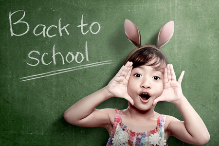 Asian student girl with funny expression standing with chalkboard background. Back to School concept