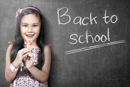 Asian student girl standing and holding candy with blackboard background. Back to School concept