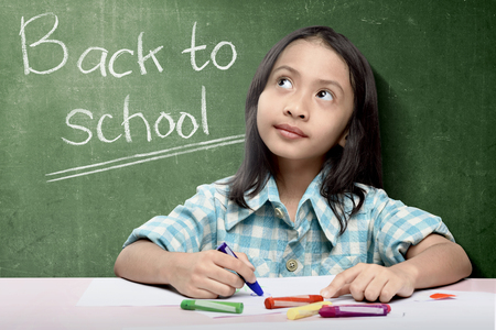 Asian student girl drawing on white paper with colorful crayons over chalkboard background. Back to School concept Imagens