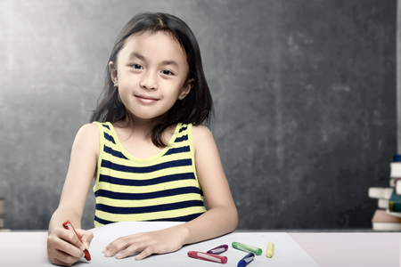 Asian student girl drawing on white paper with colorful crayons in the classroom with piles of books and blackboard background. Back to School concept