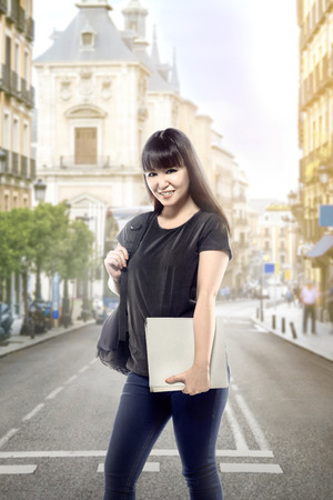 Asian student woman with backpack carrying book on city street going to campus. Back to School concept
