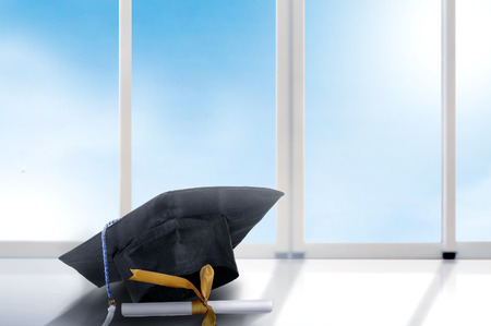 Mortarboard hat and diploma on the table with window glass and blue sky background. Graduation concept
