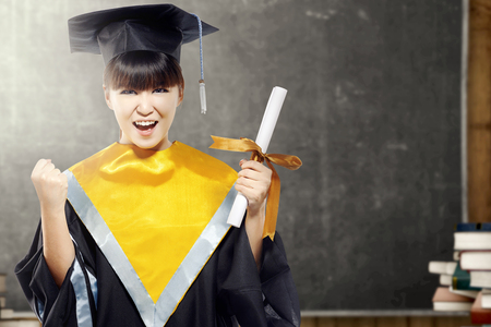 Asian woman in mortarboard hat and diploma graduating from college in the classroom with piles of books and blackboard background. Graduation concept