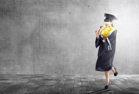 Asian woman in mortarboard hat and diploma graduating from college. Graduation concept