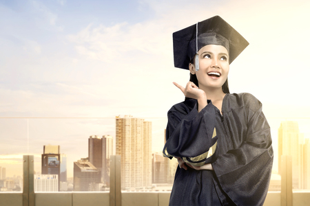 Asian woman in mortarboard hat graduating from college. Graduation concept
