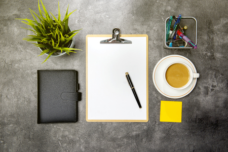 Top view of business desk with potted plant, clipboard, notebook, coffee, notes paper and business accessories on the office