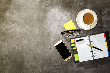 Top view of business desk with coffee, notebook, mobile phone, notes paper and eyeglasses on the office Stockfoto
