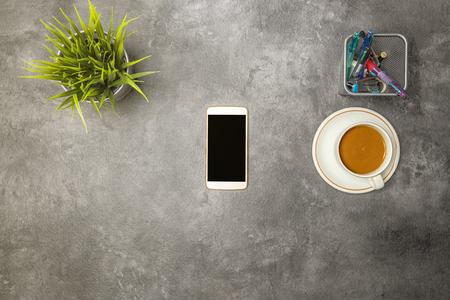 Top view of business desk with coffee, potted plant, mobile phone and business accessories on the office